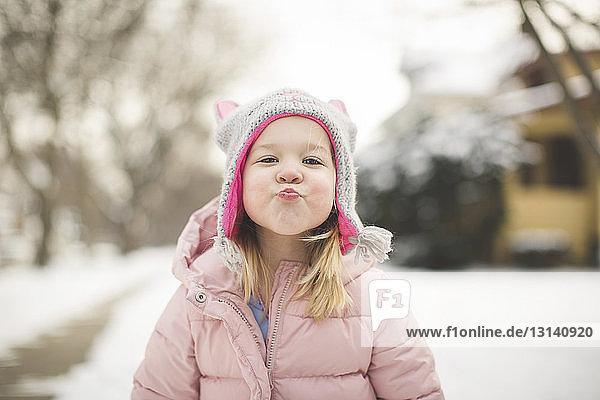 Porträt eines süßen Mädchens  das im Winter in warmer Kleidung kräuselt