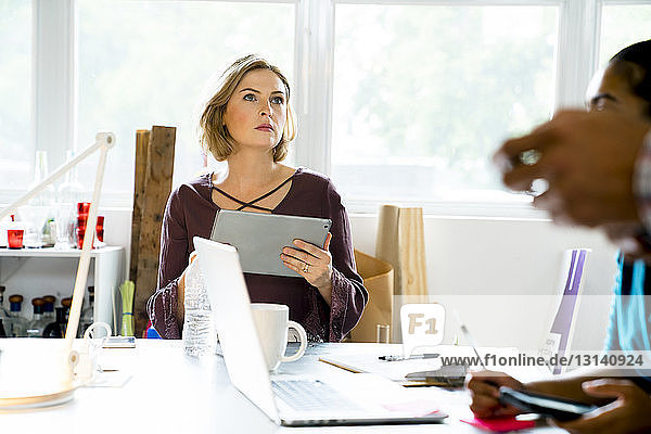 Businesswoman looking at colleagues during meeting in office