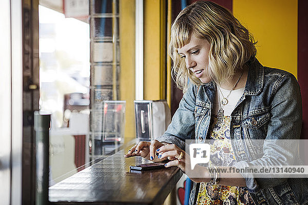 Woman using smart phone by window in cafe