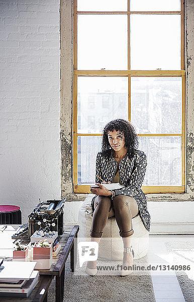 Porträt einer Geschäftsfrau  die in einem Buch schreibt  während sie im Kreativbüro sitzt