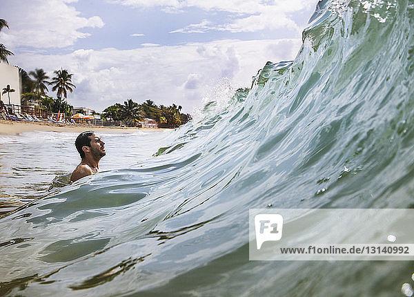 Seitenansicht eines Mannes  der die Meereswelle genießt  während er gegen den Himmel surft Seitenansicht eines Mannes, der die Meereswelle genießt, während er gegen den Himmel surft