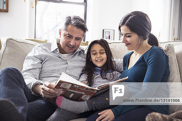 Girl with father and mother reading book while sitting on sofa at home