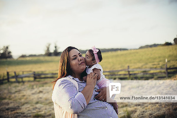 Daughter kissing mother at ranch against sky during sunset