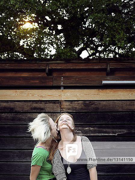 Glückliche Schwestern genießen an Holzwand