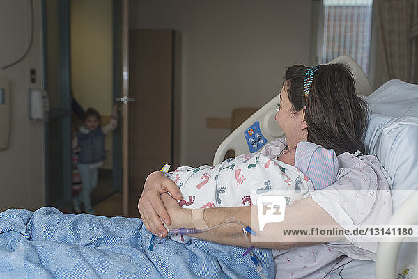Mother holding newborn son looking at daughter entering in hospital ward while relaxing on bed