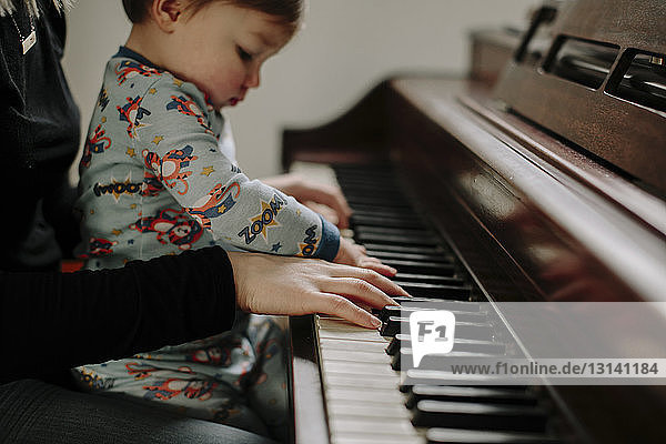 Son sitting with mother playing piano at home