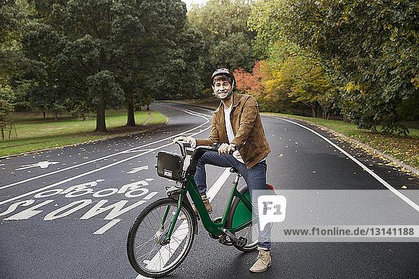 Porträt eines glücklichen Mannes mit Fahrrad auf der Strasse im Park