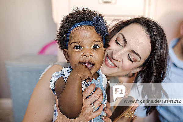 Nahaufnahme einer glücklichen Mutter,  die ihre Tochter zu Hause hält
