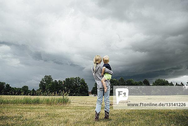 Rückansicht der Schwester  die den Bruder trägt  während sie auf einem Grasfeld vor bewölktem Himmel steht