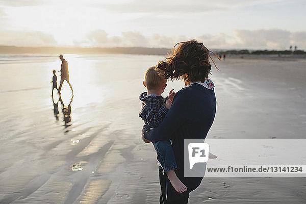 Seitenansicht einer Mutter  die einen Jungen trägt  mit Blick auf eine Familie  die am Strand spazieren geht