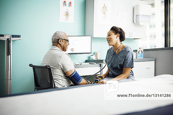 Glückliche Ärztin kontrolliert den Blutdruck eines männlichen Patienten in der Klinik