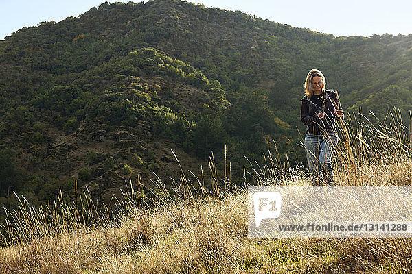 Frau hält Stock  während sie auf dem Berg steht