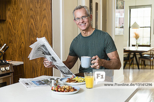 Porträt eines lächelnden  reifen Mannes  der am Esstisch sitzt und Kaffeetasse und Zeitung hält