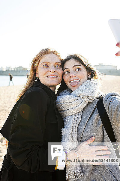 Mother and daughter taking selfie at beach