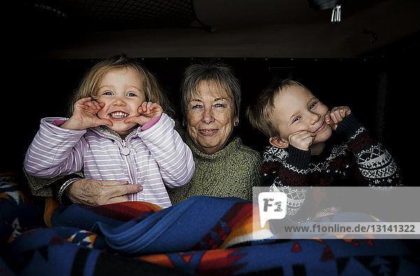 Porträt von lächelnden Enkelkindern mit Großmutter  die im Dachzelt auf dem Auto sitzen