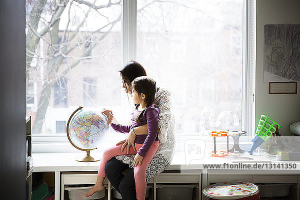 Mother showing globe to daughter against window at home