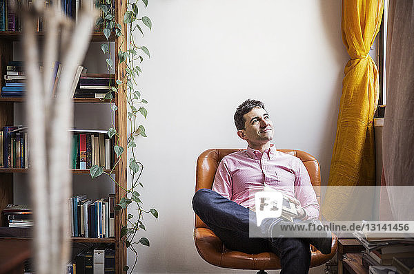 Thoughtful man holding book while sitting on chair at home
