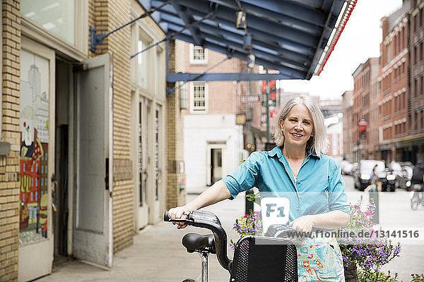 Porträt einer glücklichen reifen Frau  die mit dem Fahrrad auf dem Bürgersteig steht