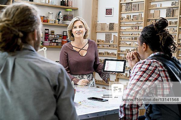 Geschäftsfrau zeigt männlichen Kollegen Daten auf Tablet-Computer