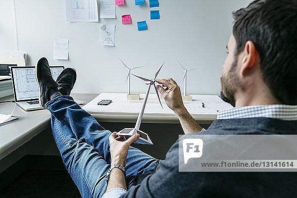 Geschäftsmann dreht Modell einer Windmühle  während er im Büro sitzt