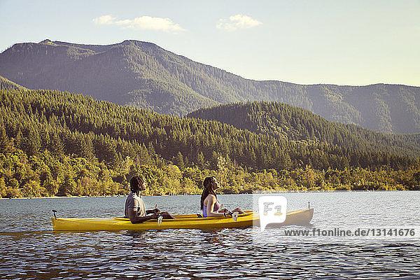Seitenansicht eines im Kanu sitzenden Paares auf einem Fluss gegen einen Berg
