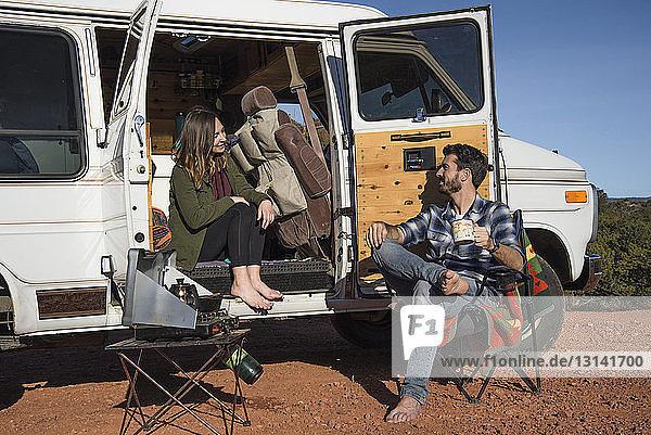 Freunde unterhalten sich  während sie auf dem Campingplatz sitzen