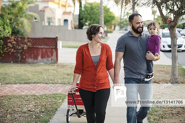 Glückliche Mutter schaut auf fröhliche Tochter  die vom Vater auf dem Fußweg getragen wird