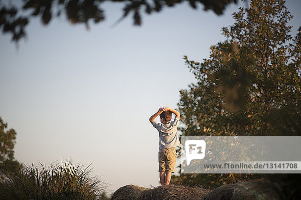 Rear view of boy with hands behind head standing on hay bale at field