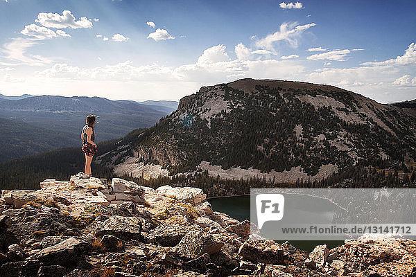 Frau steht auf einer Klippe am See gegen den Himmel