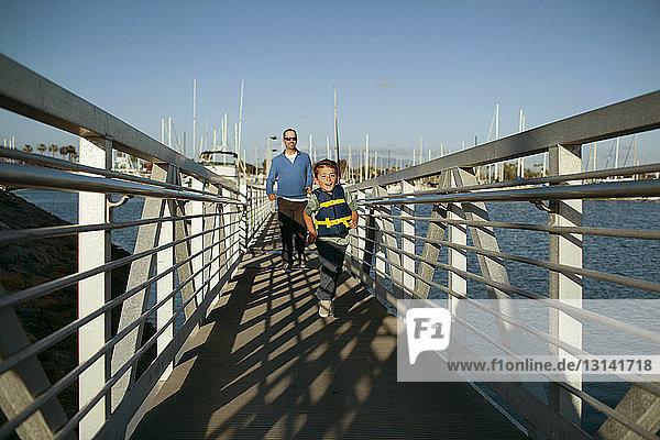 Boy with father walking on footbridge against blue sky