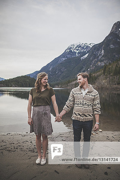Full length of smiling young couple holding hands while standing on lakeshore at Silver Lake Provincial Park