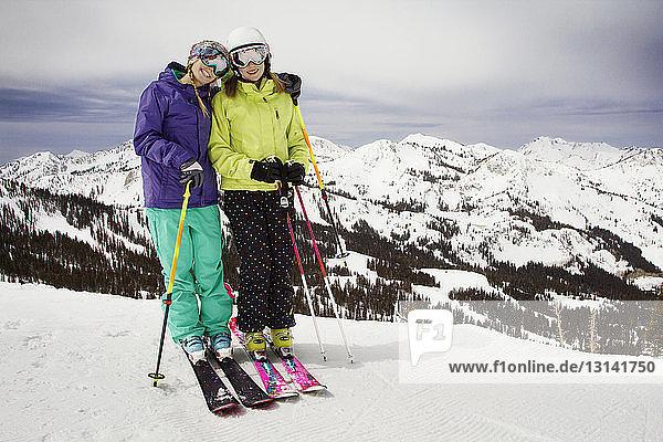 Glückliche Freunde beim Skifahren auf schneebedecktem Feld gegen Berge