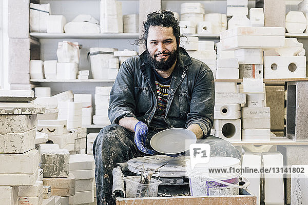 Portrait of craftsman showing earthenware in workshop