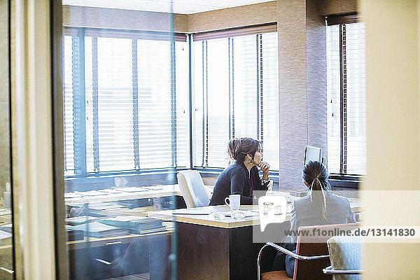Geschäftsfrau benutzt Computer  während sie mit einer Kollegin am Schreibtisch sitzt