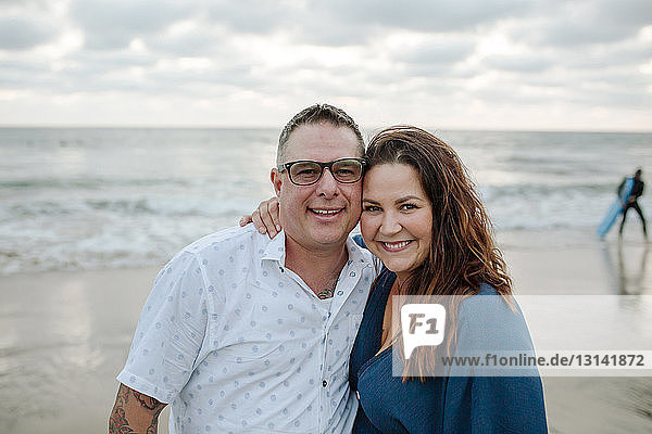 Porträt eines fröhlichen Paares am Strand vor bewölktem Himmel