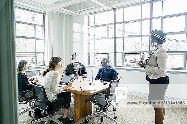 Geschäftsfrau diskutiert mit Kollegen durch Fenster gesehen