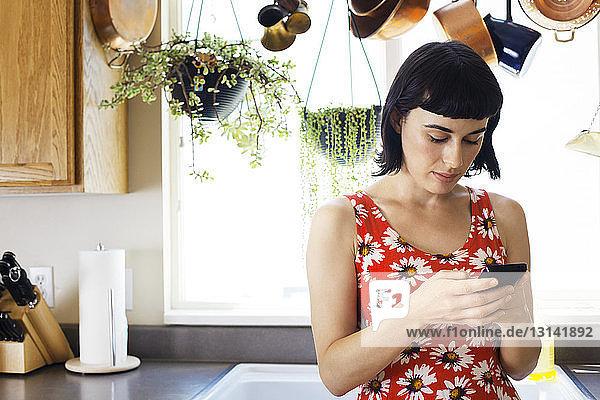 Frau telefoniert  während sie sich zu Hause an den Küchentisch lehnt