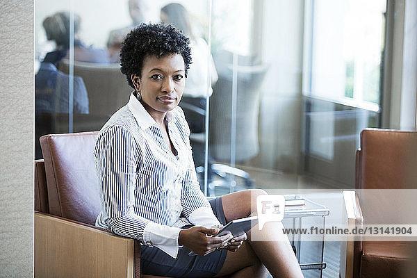 Porträt einer Geschäftsfrau  die einen Tablet-Computer im Büro hält
