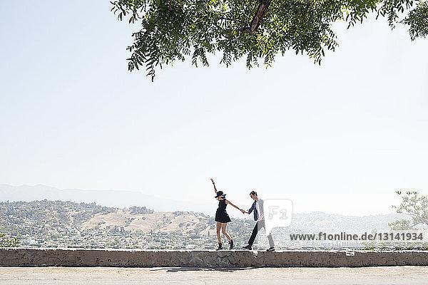 Aufgeregtes junges Paar geht auf Stützmauer gegen klaren Himmel