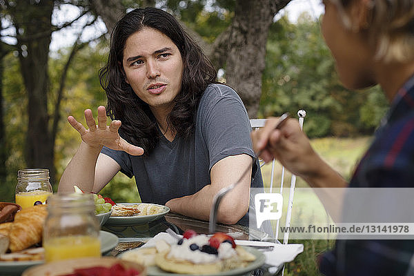 Man talking to friend while having breakfast outdoors