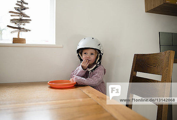 Girl wearing helmet eating food by table at home