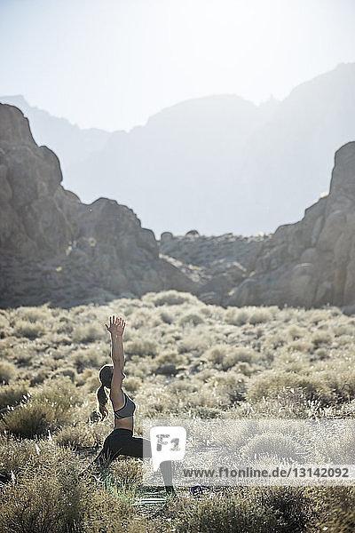 Seitenansicht einer Frau  die bei Sonnenschein Yoga auf dem Feld gegen Berge praktiziert