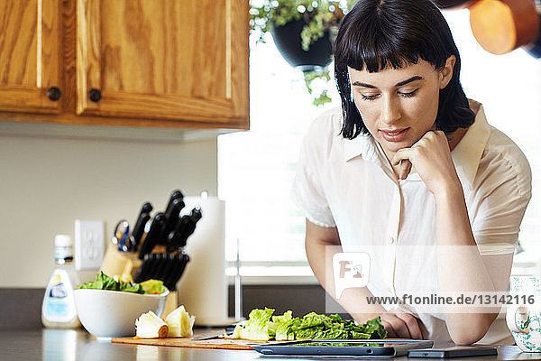 Smiling woman reading digital tablet while preparing food at kitchen in home