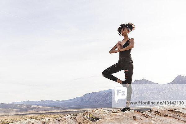 Frau meditiert  während sie auf einer Felsformation gegen den Himmel steht