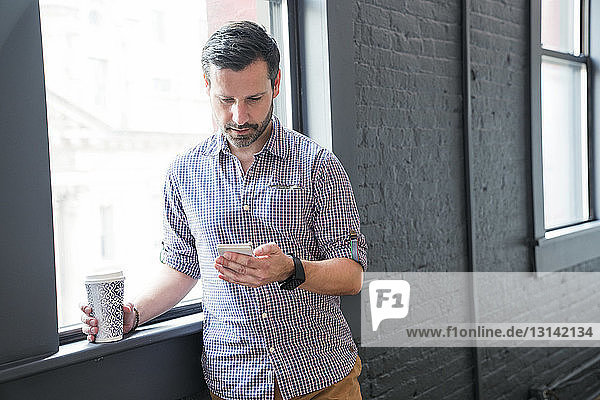 Geschäftsmann benutzt Smartphone  während er im Büro am Fenster steht