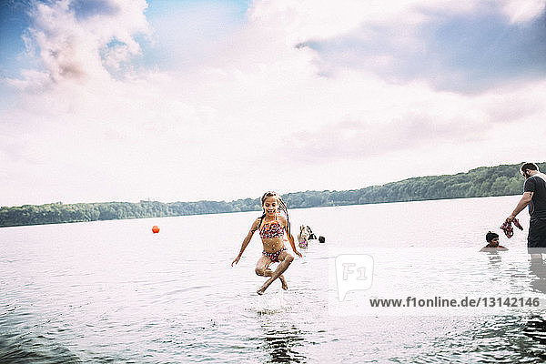 Full length of playful girl jumping in lake against cloudy sky