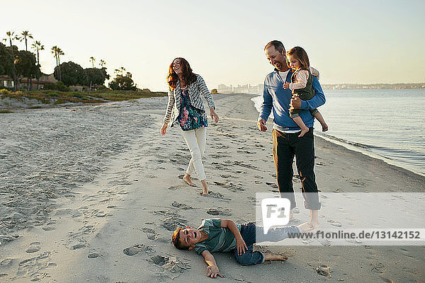 Family enjoying at beach against clear sky during sunset