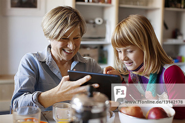 Grandmother showing tablet computer to granddaughter while sitting at table