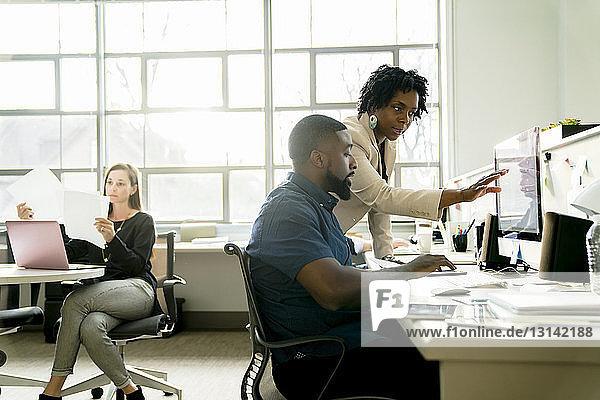 Geschäftsfrau  die einem Kollegen am Desktop-Computer erklärt
