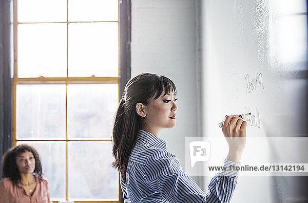Seitenansicht einer Geschäftsfrau  die in einem kreativen Büro auf Whiteboard schreibt